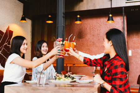 Group of Asian happy and smiling young man and women holding an alcoholic cocktail for toasting and celebrating in social party in restaurant Фото со стока - 105388615