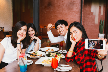 Group of Happy Asian male and female friends taking a selfie photo and having a social toast together in restaurant Standard-Bild - 105388638