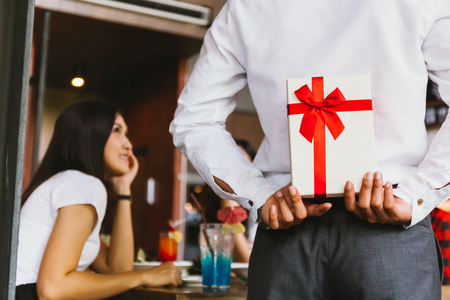 Asian woman expected to receive a surprise present gift box from man as a romantic couple for occasional anniversary celebration