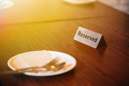 'Reserved' Sign on dining table in restaurant with spoon, fork and plate