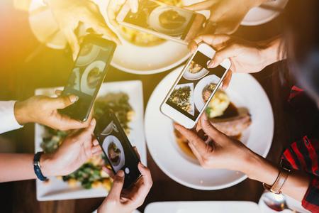 Grupo de amigos saliendo y tomando una foto de comida italiana junto con el teléfono móvil