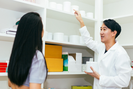 Asian pharmacist doctor in professional gown explaining and giving advice with female client in drugstore shop