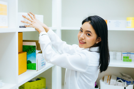 Cute Asian female pharmacist doctor working on medical health products in drugstore shop