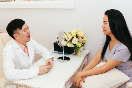 Asian doctor discussing and consulting with Asian patient seeking for help in hospital examination room