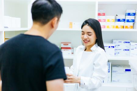 Aziatische vrouwelijke apotheker arts in professionele jurk uitleggen en advies geven met mannelijke cliënt in drogisterij winkel Stockfoto
