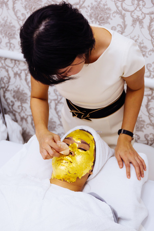 Beauty clinic staff helping young woman getting 24 karat gold facial treatment at the beauty clinic. The treatment of using real gold for youthful skin Reklamní fotografie - 105455384