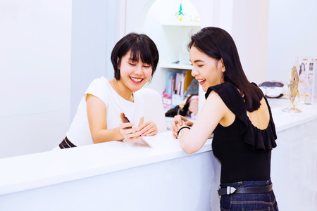 Asian front desk lobby receptionist talking and discussing with beautiful happy Asian female client