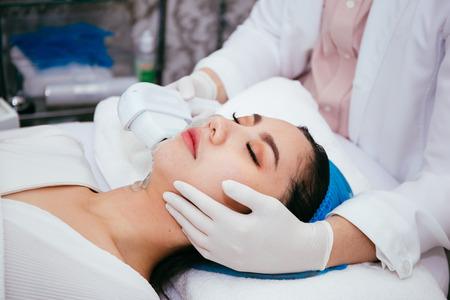 Jonge Aziatische vrouw die IPL en laserbehandeling krijgt door schoonheidsspecialiste bij schoonheidskliniek