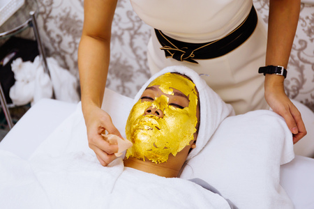 Beauty clinic staff helping young woman getting 24 karat gold facial treatment at the beauty clinic. The treatment of using real gold for youthful skin 版權商用圖片 - 105455389