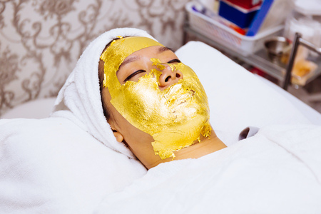 Young woman getting 24 karat gold facial treatment at the beauty clinic. The treatment of using real gold for youthful skin Stock Photo