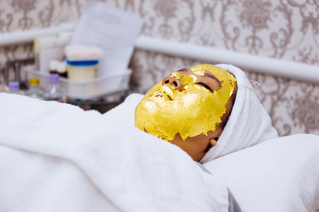 Young woman getting 24 karat gold facial treatment at the beauty clinic. The treatment of using real gold for youthful skin Banco de Imagens