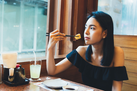Attractive Asian woman sitting and eating Japanese food alone in the restaurant