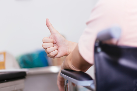 Close up of male patient on wheelchair giving thumbs up as a sign of happy support