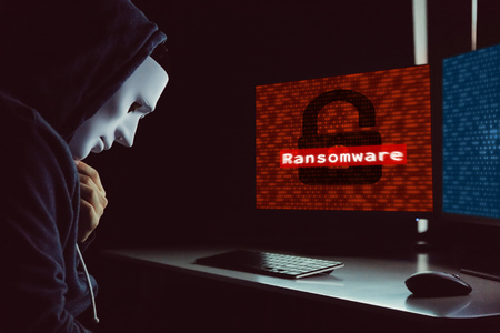 Masked hacker under hood using computer to hack into system and employ ransomware - internet computer crime concept
