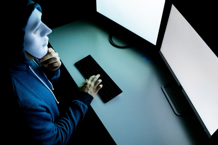 Top view of male hacker in mask under hood using computer to hack into system and trying to commit computer crime - Hacker and computer threat crime concept 写真素材