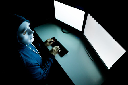 Top view of male hacker in mask under hood using computer to hack into system and trying to commit computer crime - Hacker and computer threat crime concept 版權商用圖片