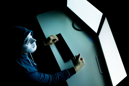 Hacker in mask under hood having many credit cards in computer room - with copy space on blank screen to insert text ,word, and pictures