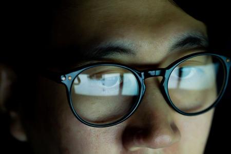 Cerca de joven asiático con gafas viendo videos y navegando por internet en un dispositivo tecnológico en la oscuridad Foto de archivo