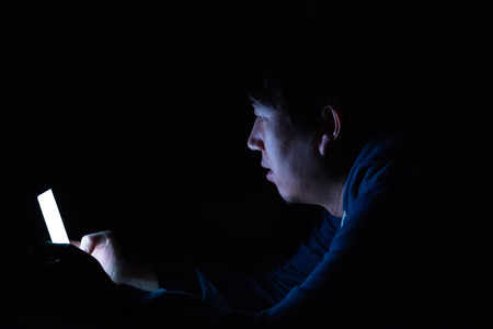 Asian young man using phone in dark bedroom with blue light phone screen - unhealthy eyes strain concept Stockfoto