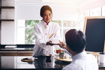 Young Asian female barista making and giving coffee to male customer. Business man receiving coffee at cafe restaurant