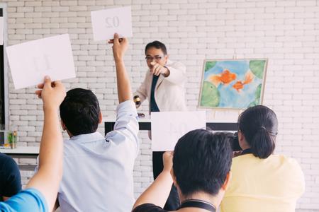 Grupa ludzi licytujących podczas publicznego wydarzenia sprzedaży licytacji. Ludzie siedzący i starający się licytować najwyższą cenę za malowanie na aukcji