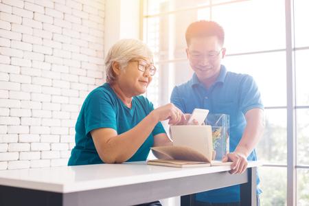 Starszy rodzic używa telefonu, podczas gdy jej syn uczy i pokazuje, jak używać. Szczęśliwa rodzina dobrze się bawi