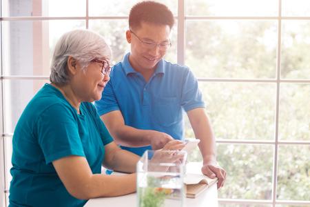 Padre mayor que usa el teléfono mientras su hijo está enseñando y mostrando cómo usarlo. Familia feliz pasando un buen rato Foto de archivo
