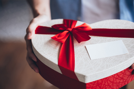 Close up of man hands giving a decorative present giftbox with empty white card - with copy space to insert text Archivio Fotografico - 105996789