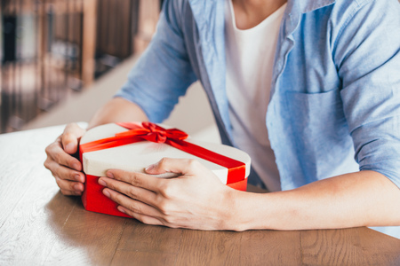 Young man sitting in cafe restaurant and holding a present gift giving to someone special for special occasion