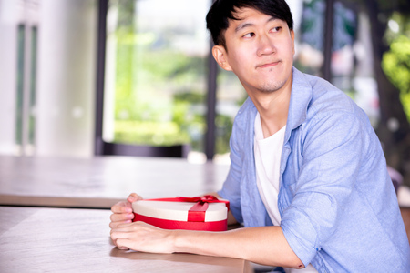 Young Asian man patiently sitting in cafe restaurant and holding a present gift giving to someone special for special occasion Stok Fotoğraf