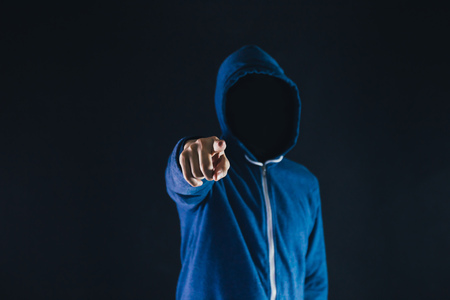 Anonymous and faceless man under hoodie pointing finger at camera isolated over dark background - incognito and mysterious criminal on internet activities concept Reklamní fotografie