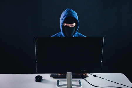Unrecognizable masked man under hoodie using a computer - data thief and online activity hacking