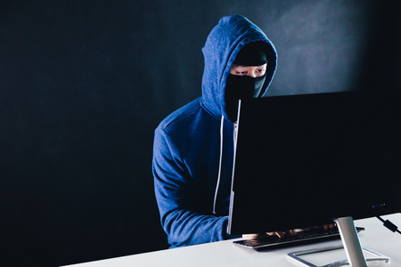 Unrecognizable masked man under hoodie using a computer - data thief and online activity hacking Stock Photo - 115237415