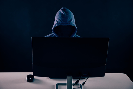 Anonymous and faceless hacker under hoodie using computer isolated over dark background - illegal online internet criminal concept