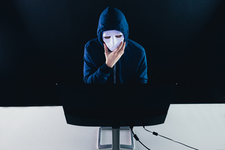 Anonymous and masked hacker under hoodie using computer isolated over dark background - illegal online internet criminal concept