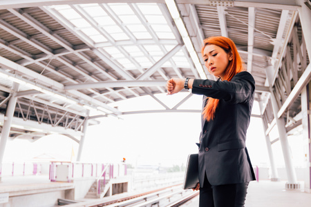 Young Asian businesswoman in formal suit waiting for train to arrive and looking at watch to check time for avoid late at work Stock Photo