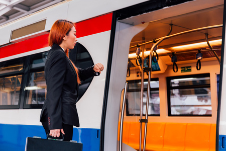 Young Asian businesswoman in formal suit waiting for train to arrive and looking at watch to check time for avoid late at work