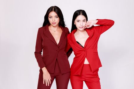 Two young attractive Asian female models in stylish fashionable suit posing together in white isolated background