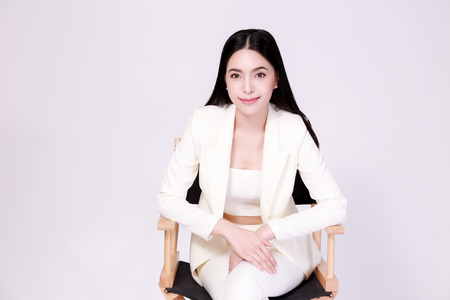 Young confident Asian woman in all white elegant suit with pants posing sitting in half body isolated over white background