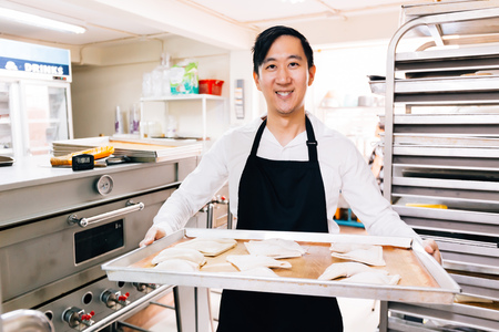 Young Asian male bakery shop chef smiling and looking at the camera while holding a tray of breads in kitchen in bakery shop scene Stockfoto