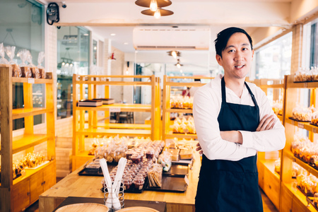 Young Asian male bakery shop merchant business owner smiling and looking at the camera in bread store Imagens