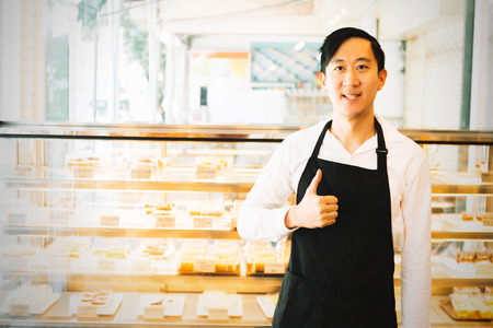 Asian cafe restaurant shop owner giving thumbs up with assortments of cakes behind - small business entrepreneur concept Stock Photo