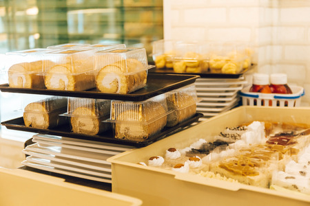 Many assortments of sweet dessert cakes and cream rolls prepared to be displayed and decorated in cafe restaurant