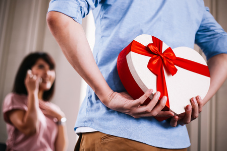 Close-up of Young man hiding a present gift box with red ribbon to surprise girlfriend unexpectedly - couple event anniversary surprise concept