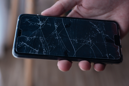 Close-up of human hand holding a broken and damaged glass of mobile phone from accident