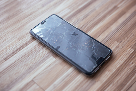 Close-up of broken and damaged glass of mobile phone from accident on floor Banco de Imagens