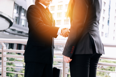 Professional business woman and man in formal suit shaking hands in outdoor city buildings - Closing deal and business cooperation concept