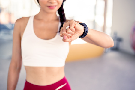 Close up of young Asian active fit woman in sports bra checking smartwatch inside gym - modern technology fitness lifestyle concept