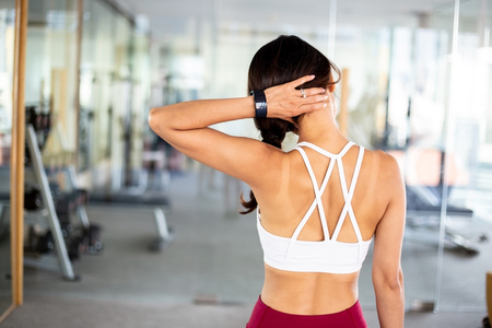 Rear view of young sporty fit woman in sportswear touching on neck during workout exercise in gym - neck pain from workout concept
