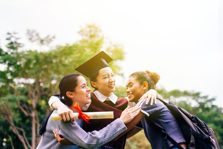 Smiling and happy diverse racial classmate friends hugging successful Asian female graduate with formal graduation hat together in the park during summer